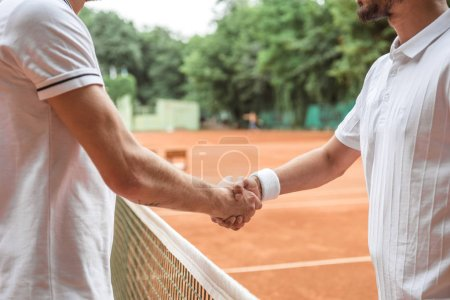 cropped view of tennis players shaking hands after game on court