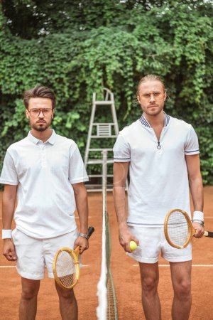 serious sportsmen with wooden rackets and ball posing after game on tennis court