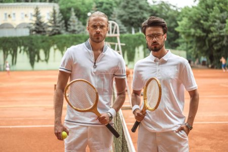serious tennis players with wooden rackets and ball posing after game on court
