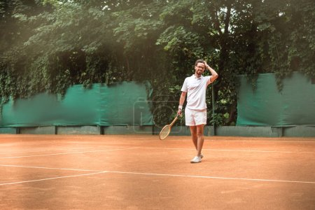 handsome tennis player with racket standing on tennis court