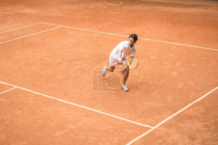 Photo for Handsome tennis player training with wooden racket on brown court - Royalty Free Image