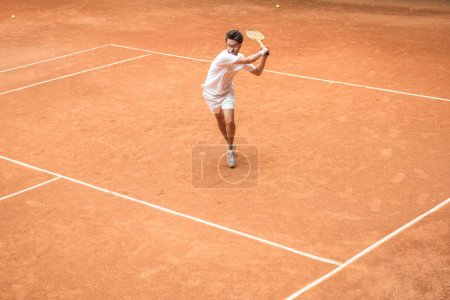 Photo for Old-fashioned tennis player training with wooden racket on brown court - Royalty Free Image