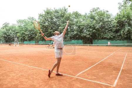 handsome tennis player with racket throwing ball on tennis court