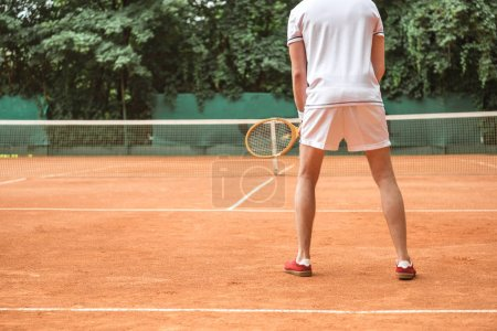 back view of tennis player with racket on tennis court with net