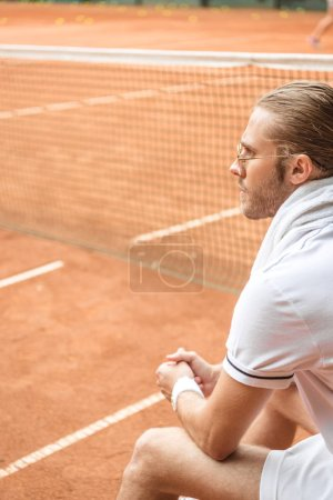 old-fashioned tennis player with towel resting on brown tennis court with net