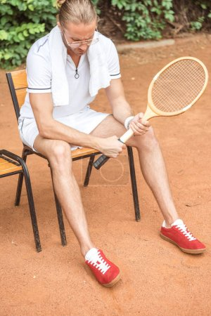 handsome tennis player with towel and tennis racket resting on chair on tennis court