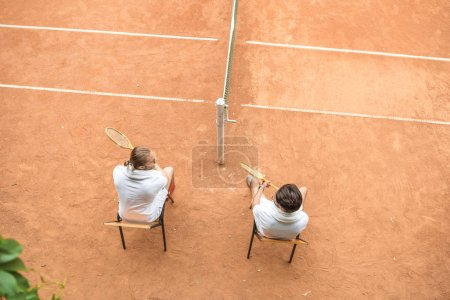 overhead view of tennis players with wooden rackets resting on court