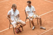 tennis players with towels and wooden rackets resting on chairs on brown court