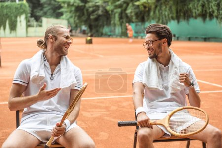 smiling tennis players with towels and wooden rackets resting on chairs