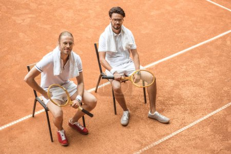 tennis players with vintage wooden rackets resting on chairs