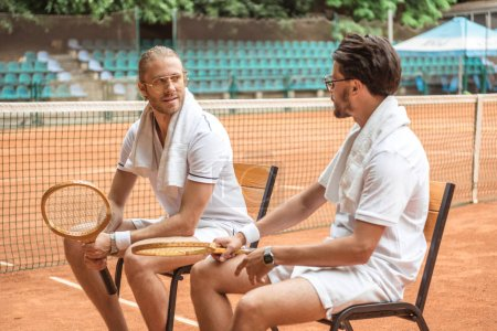 handsome athletic tennis players with retro wooden rackets resting on chairs