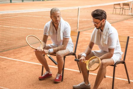 old-fashionedtennis players with retro wooden rackets resting on chairs