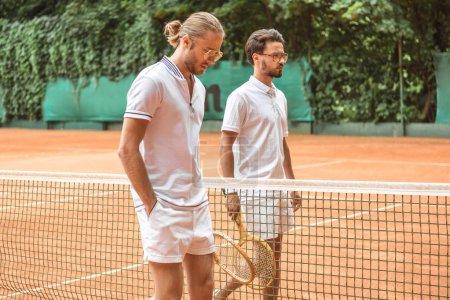 tennis players in white sportswear with wooden rackets walking near net on court