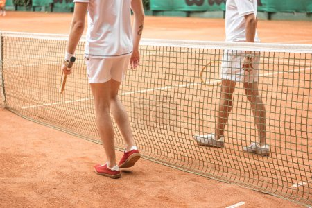 cropped view of tennis players with wooden rackets walking near net on court