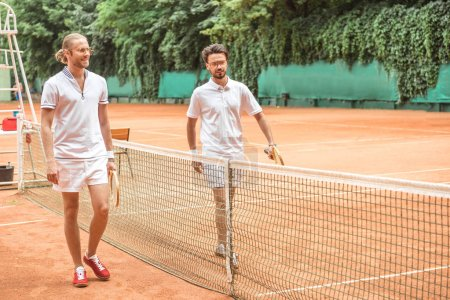 tennis players with wooden rackets walking after training near net on court