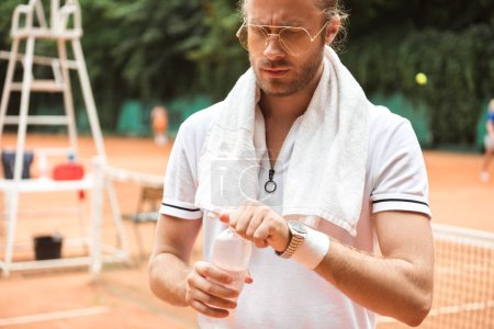 handsome tired tennis player with towel and water on tennis court