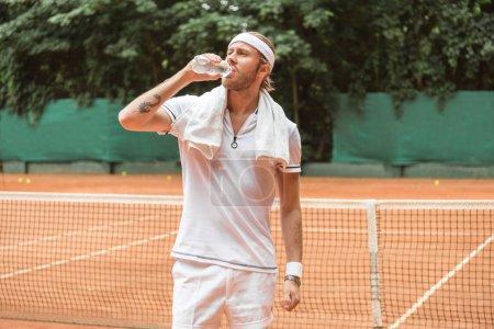 Photo pour Joueur de tennis fatigué de style rétro avec serviette d'eau potable sur le court de tennis - image libre de droit