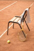 close up of chair with tennis ball, retro wooden racket and towel on tennis court