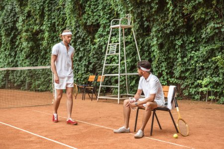 old-fashioned tennis players in white sportswear on court