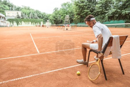 tennis player sitting on chair with tennis ball, retro wooden racket and towel on court
