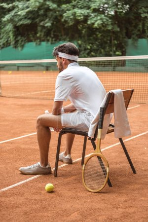 tennis player in white sportswear resting on chair with tennis ball, retro wooden racket and towel on court