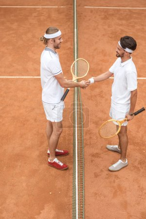 tennis players with wooden rackets shaking hands after game on court