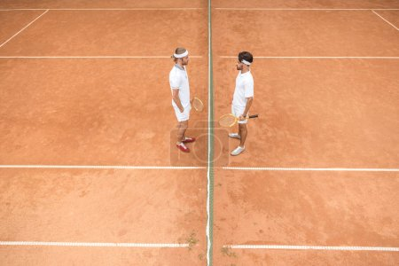 overhead view of tennis players in white sportswear with wooden rackets on court
