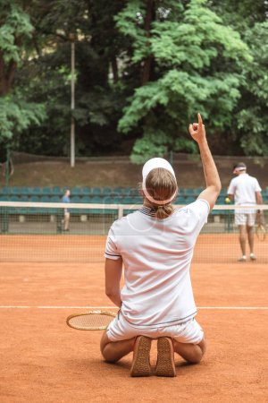 Photo for Old-fashioned tennis player gesturing up and kneeling after winning match on court - Royalty Free Image
