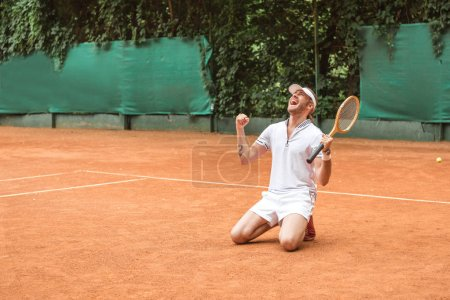 Photo for Blond winner with racket celebrating and kneeling on tennis court - Royalty Free Image