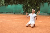 blond winner with racket celebrating and kneeling on tennis court