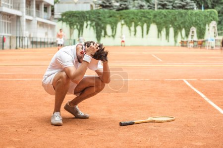 Photo for Tennis player losing match on court with racket - Royalty Free Image