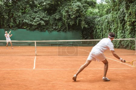 old-fashioned sportsmen playing tennis with wooden rackets on court