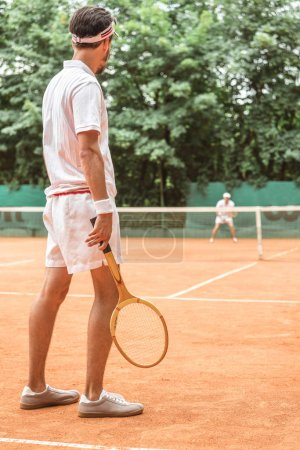 back view of man playing tennis with wooden racket on tennis court