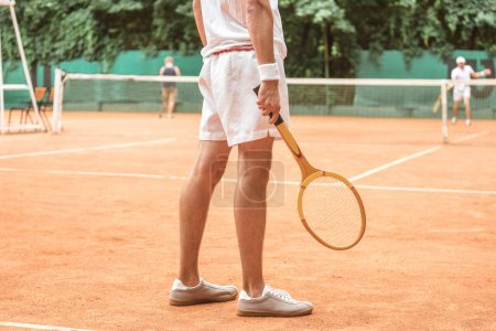 cropped view of tennis player holding retro wooden racket and standing on tennis court