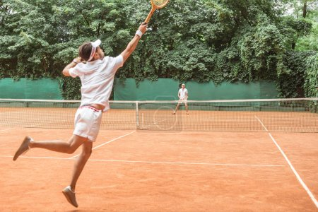 sportsman jumping while playing tennis with friend on court