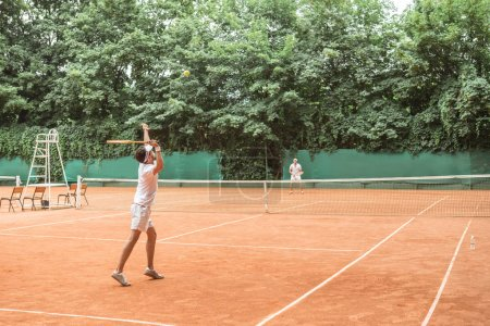 sportsmen playing tennis with wooden rackets on court