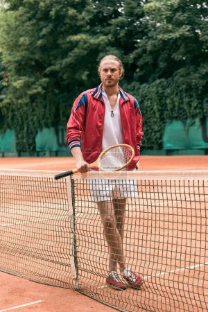retro styled man with tennis racket standing at net on tennis court