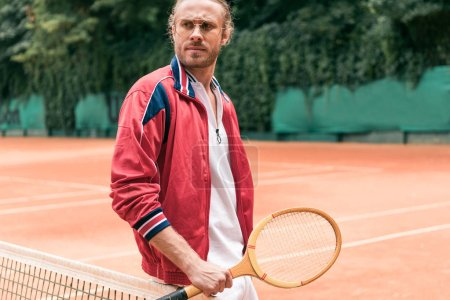 handsome man with wooden tennis racket standing at net on tennis court
