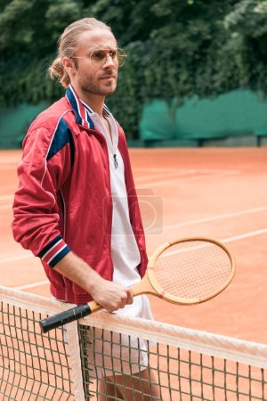 handsome retro styled tennis player with wooden racket standing at net on tennis court