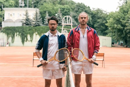 old-fashioned friends with wooden rackets posing on tennis court with net