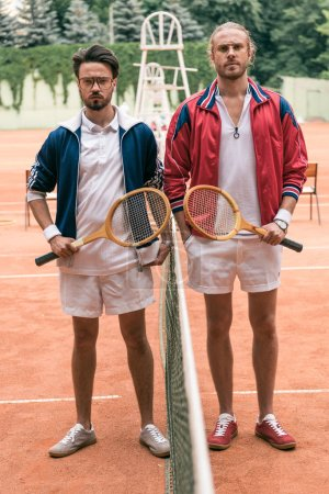 retro styled friends with wooden rackets posing on tennis court with net