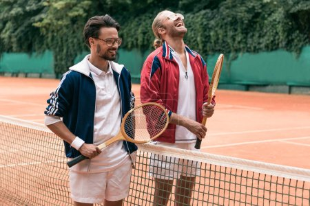laughing retro styled friends with wooden rackets on tennis court with net