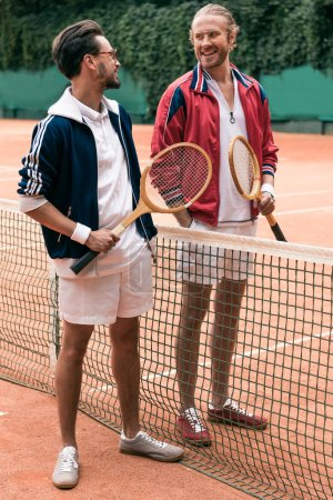 Photo for Smiling friends with wooden rackets walking on tennis court with net - Royalty Free Image