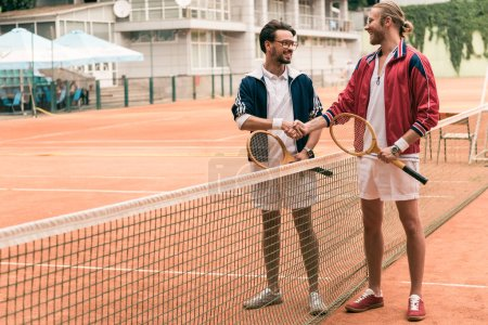 friends with wooden rackets shaking hands on tennis court with net