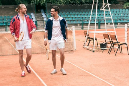 athletic friends with wooden rackets walking on tennis court