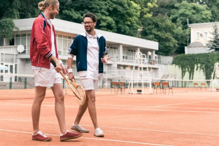 Photo for Athletic retro styled friends with wooden rackets talking and walking on tennis court - Royalty Free Image
