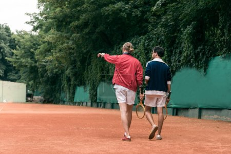 back view of retro styled friends with wooden rackets walking on tennis court
