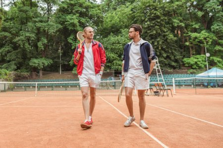 retro styled friends with wooden rackets walking on tennis court