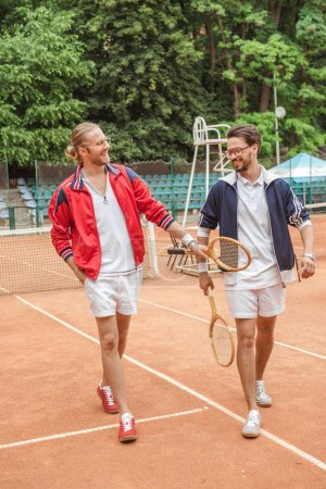 smiling friends with wooden rackets walking on tennis court