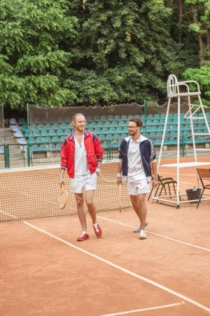 old-fashionedfriends with wooden rackets walking on tennis court